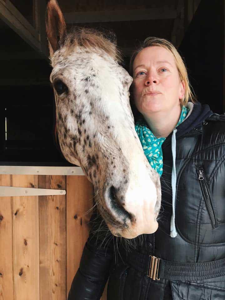 Natalie Hodges cuddling a horse.