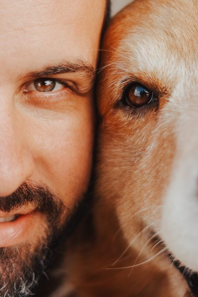 Man and dog faces next to each other both smiling